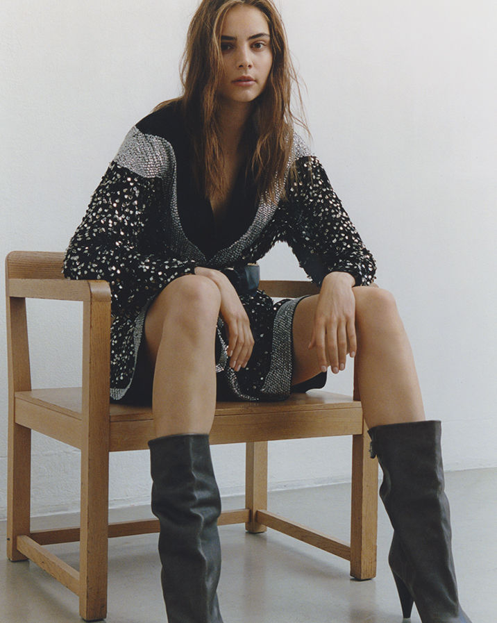 Model is sitting on a chair, wearing the Caldes dress and the Lacine boots.
