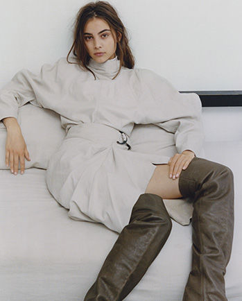 Model is sitting on a sofa, wearing the Caby top, Fiova skirt and Lacine boots.