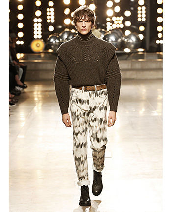 Model is walking the runway, wearing the Kentow sweater, the Jack trousers, the Djubih belt and the Camp boots.