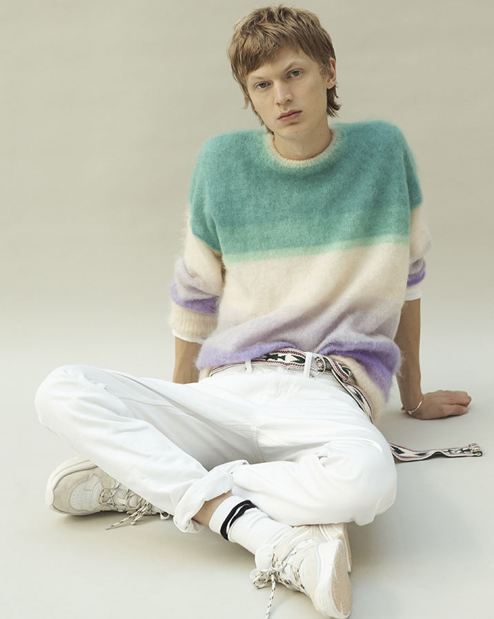The model is sitting on the floor, wearing the Drussellh knitwear, the Jack jean and th Kindsayh sneakers.