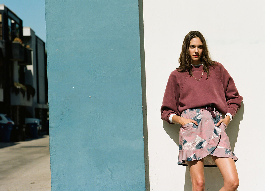 The model is leaning agaisnt a wall, wearing the Bradford sweat and the Roan skirt.