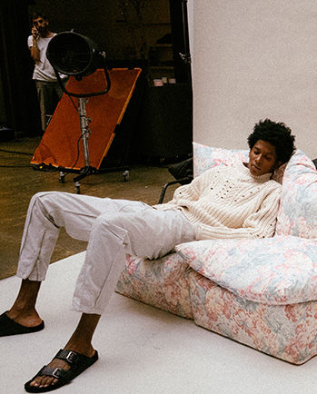 The model is sitting, wearing the Nuko pull, the Tilsen pants and the Lekson sandals.