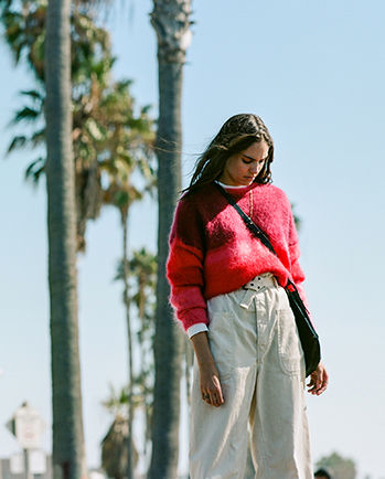 The model is walking, wearing the Drussel knitwear, the Rinny pants and the Lecky bag.