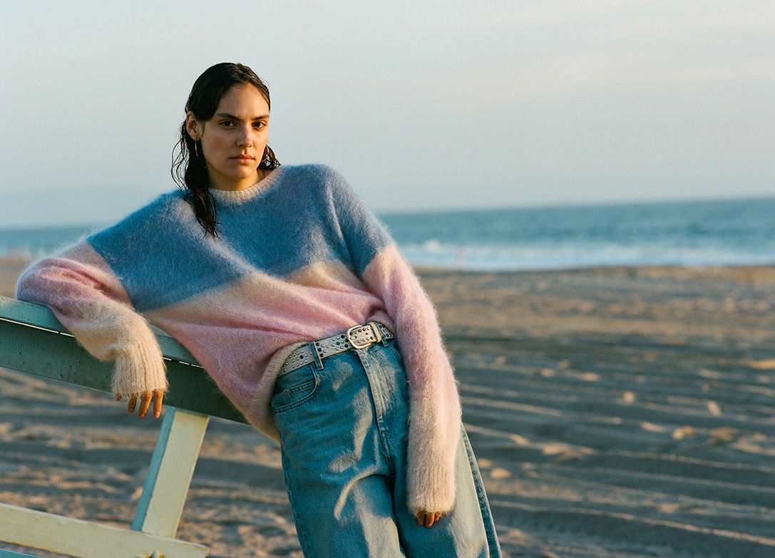 The model is standing, next to a barrier, wearing the Drussel knitwear and the Corsyj pants.