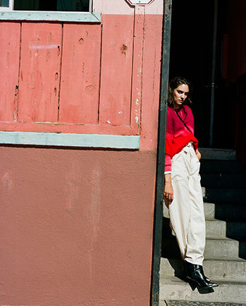The model is standing, wearing the Drussell knitwear and the Rinny pants.