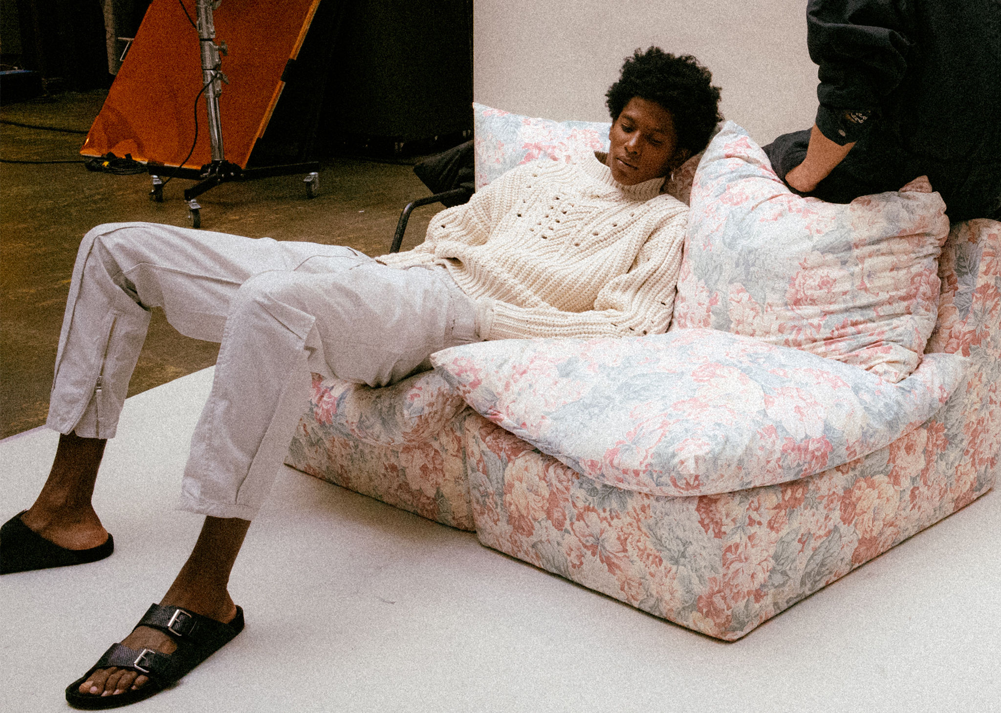 The model is sitting on a sofa, wearing the Nuko knitwear, the Tilsen trousers and the Lekson sandals. Click on this picture to see the new Isabel Marant Men Spring-Summer 2020 selection.