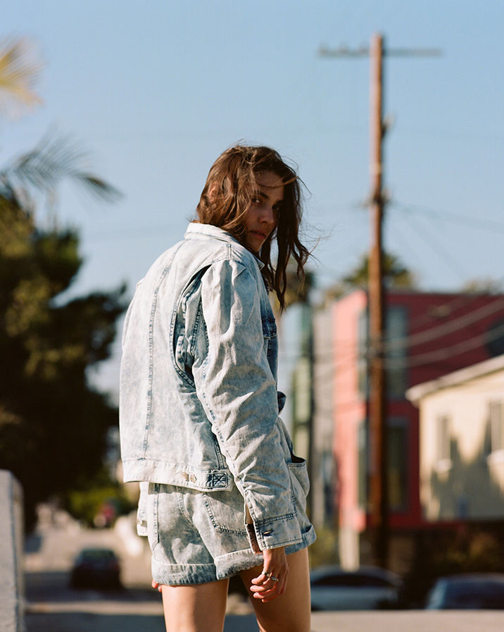 The model is walking, wearing the Harmon jacket and the Itea short.