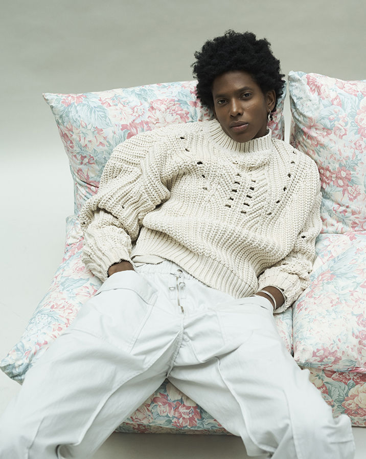 The model is sitting on a sofa, wearing the Nuko knitwear and the Tilsen trousers.