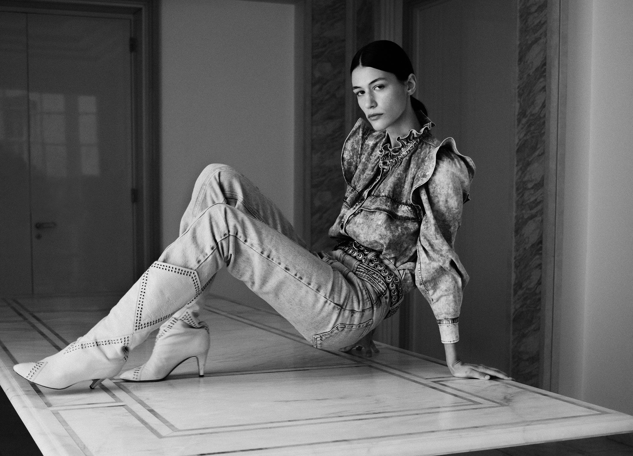 The model is sitting on the floor, wearing  the Idety shirt, the Henoya pants and Lahia boots.