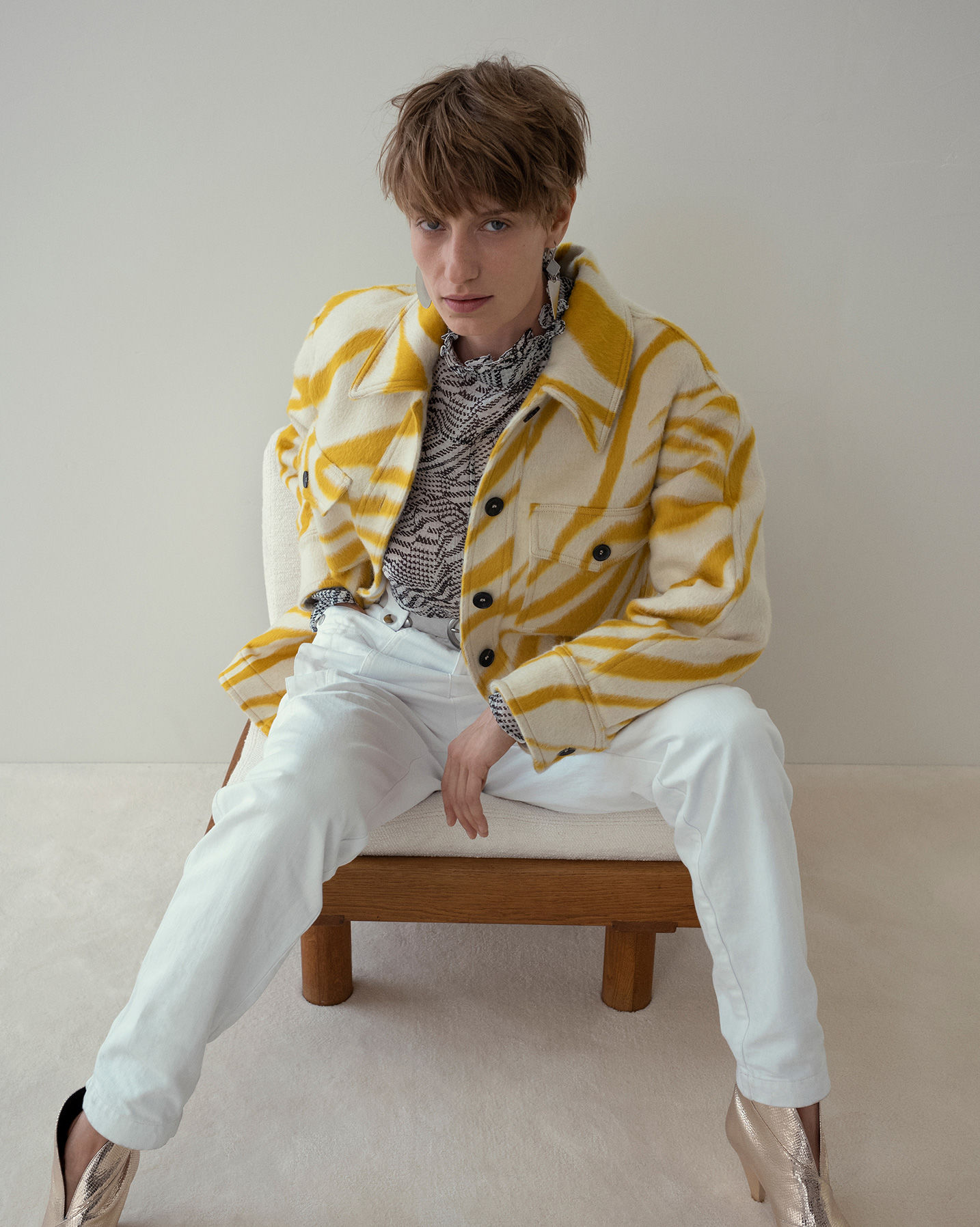 The model is sitting wearring the Harvey coat, the Emsley top and the Kerris trousers.