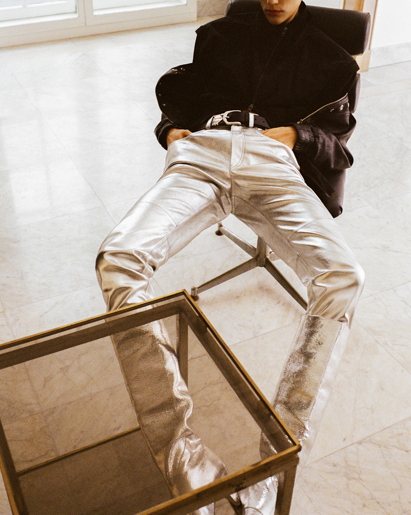 The model is sitting, wearing the Qlerie Jacket, the Wayne pants and the Laomi boots.