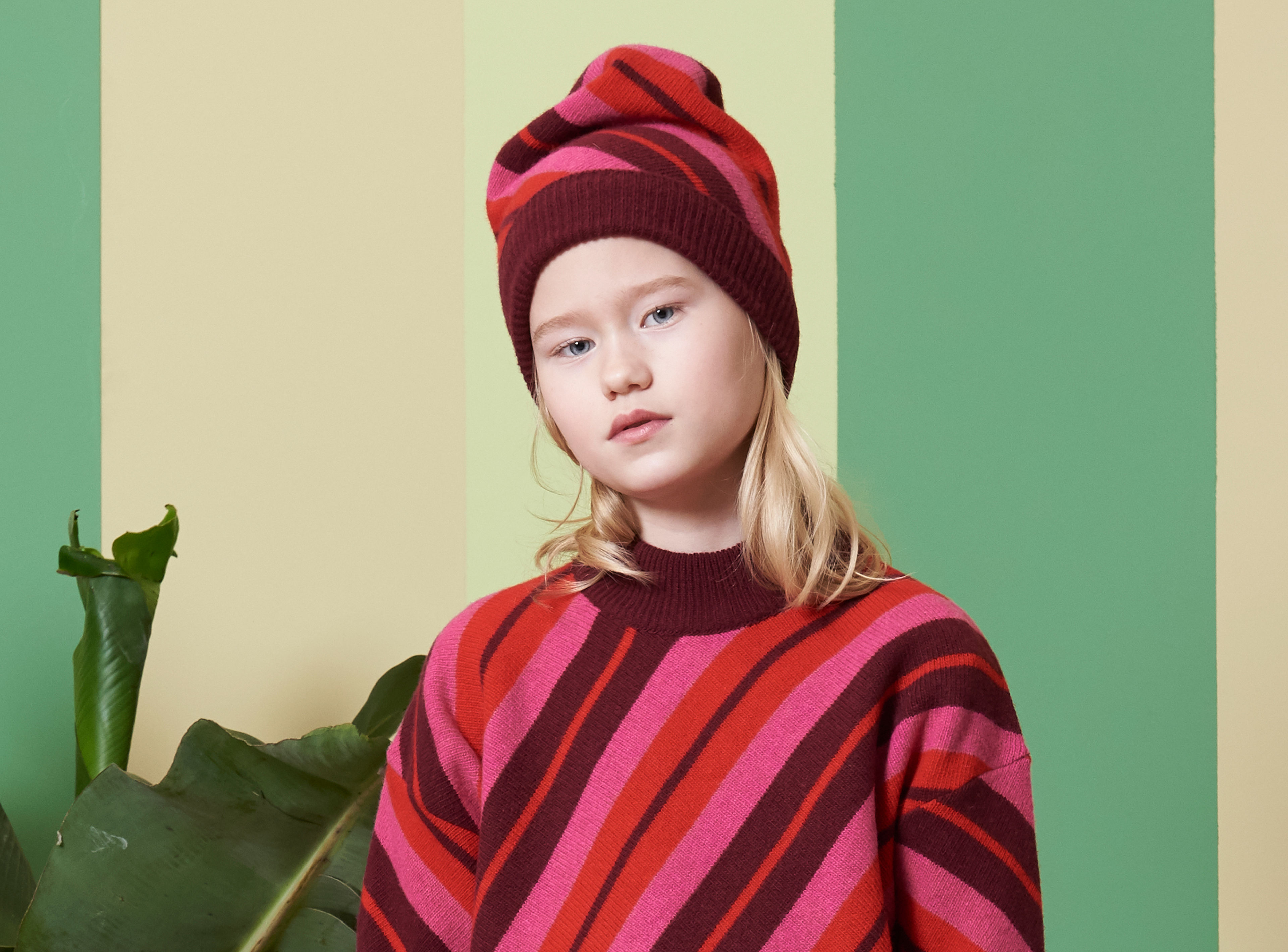 Girl wears multicolour wool hat with pink stripes