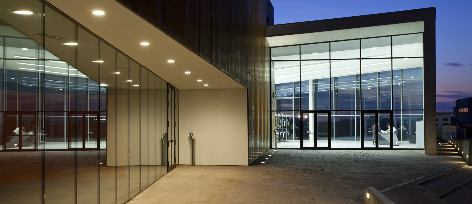 Large glass front entrance of building with lit up interior at night.