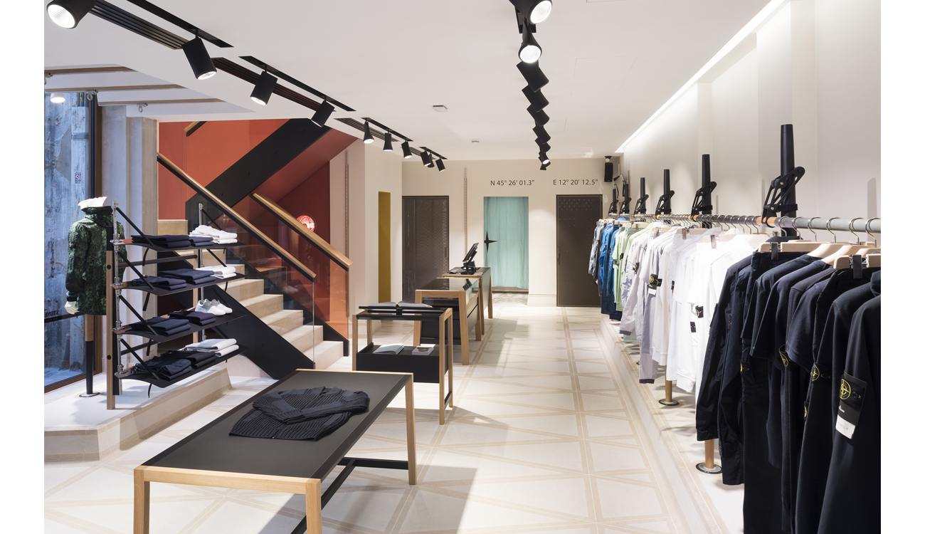 Store interior with rows of dark blue, ceiling spotlights, a white ceiling and stone floor tiles, a staircase and minimalist store fittings.