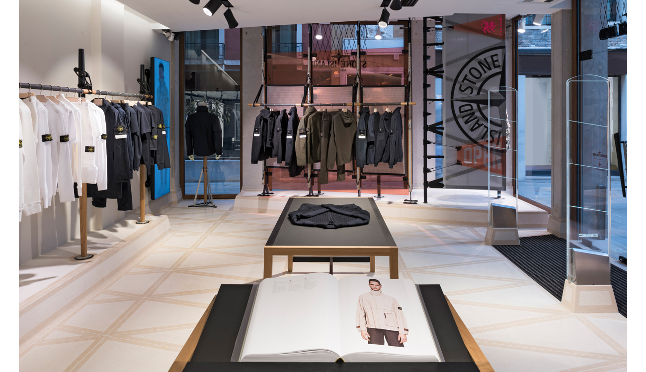 Store interior with large vertical banner showing the Stone Island compass logo and the Stone Island Archive open on a table.