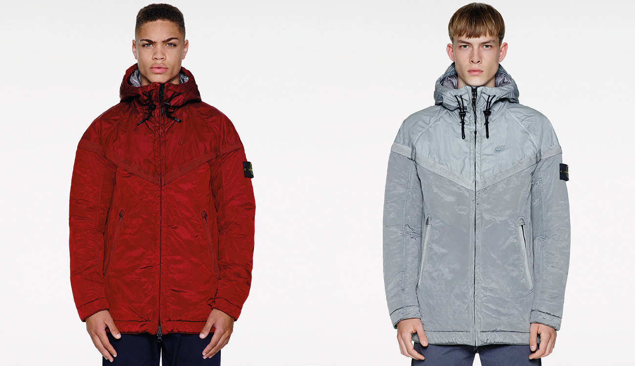 Two models, one wearing a red monochrome Nike Windrunner jacket and one in a gray monochrome Nike Windrunner jacket.