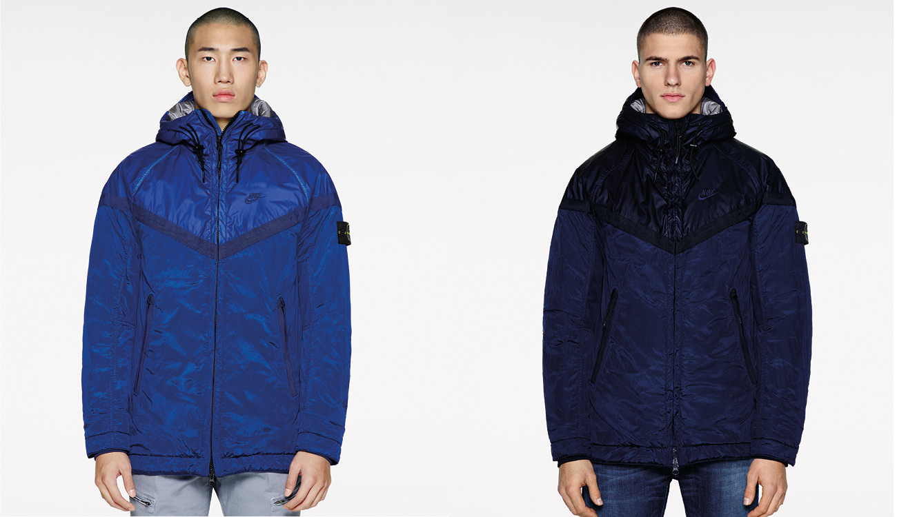 Two models, one wearing a blue, monochrome Nike Windrunner jacket and one in a navy, monochrome Nike Windrunner jacket.
