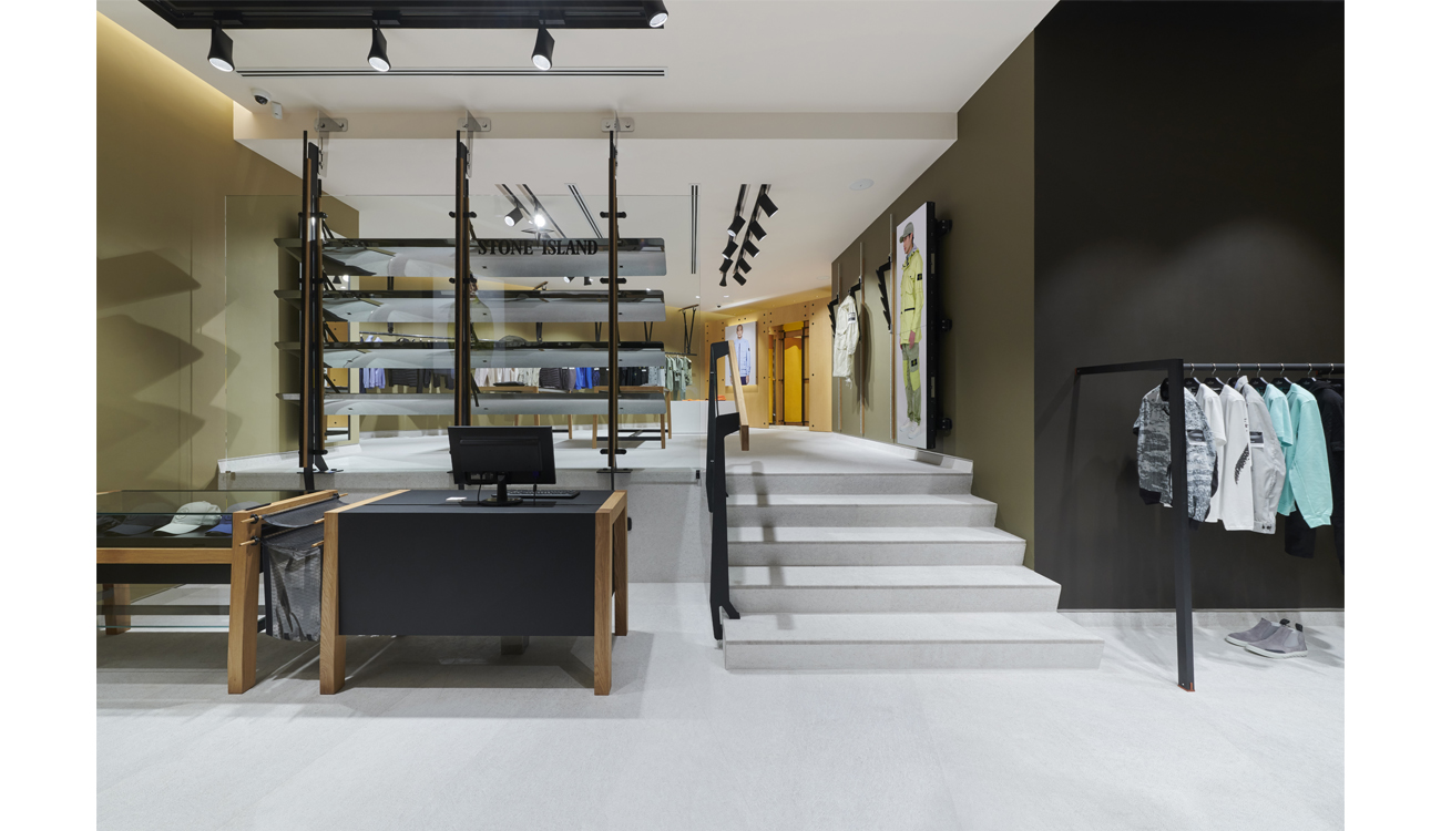 Contemporary store interior with white ceiling and floor, different colored walls, part of the store on a raised platform and minimalist store fittings.