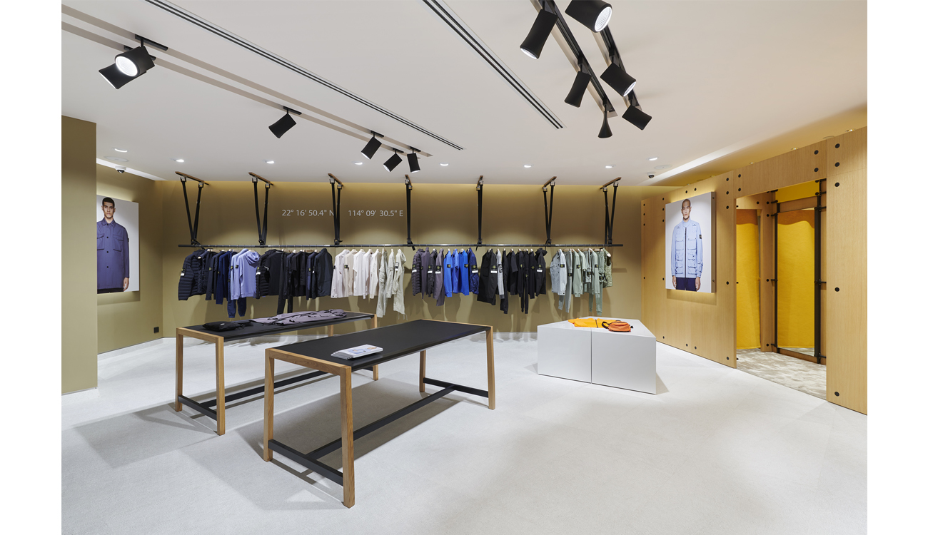 Row of clothes racks suspended from the ceiling along back wall, changing rooms on right side and tables in the center.
