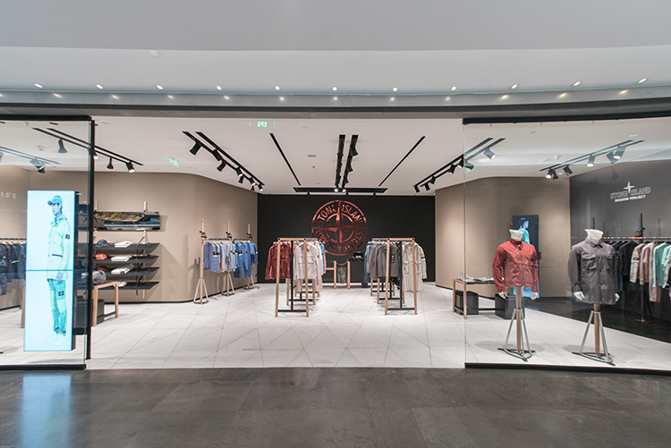 Store entrance wide open leading to brightly lit store with the Stone Island compass logo on back wall.