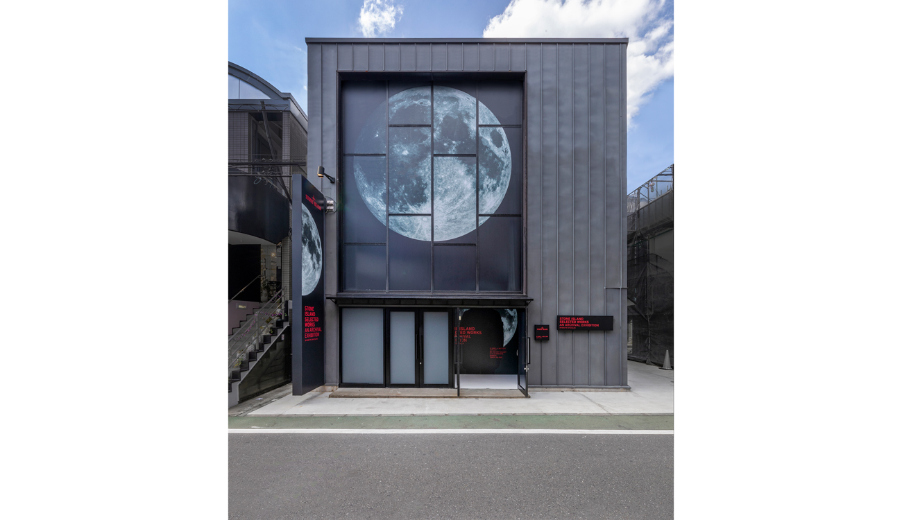 Street view of the dark colored exteriors of the exhibition space, with a large image of the moon.