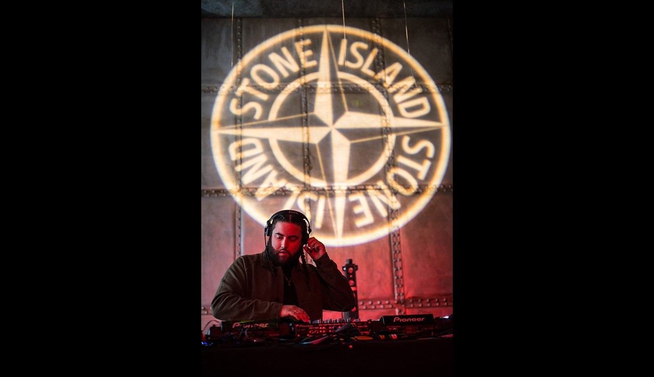 DJ playing under Stone Island compass logo projected on the wall.