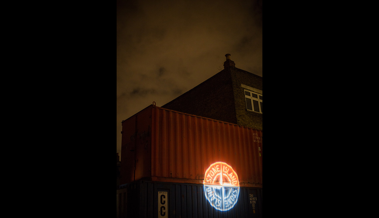 Stone Island compass logo projected on large red and blue steel containers.