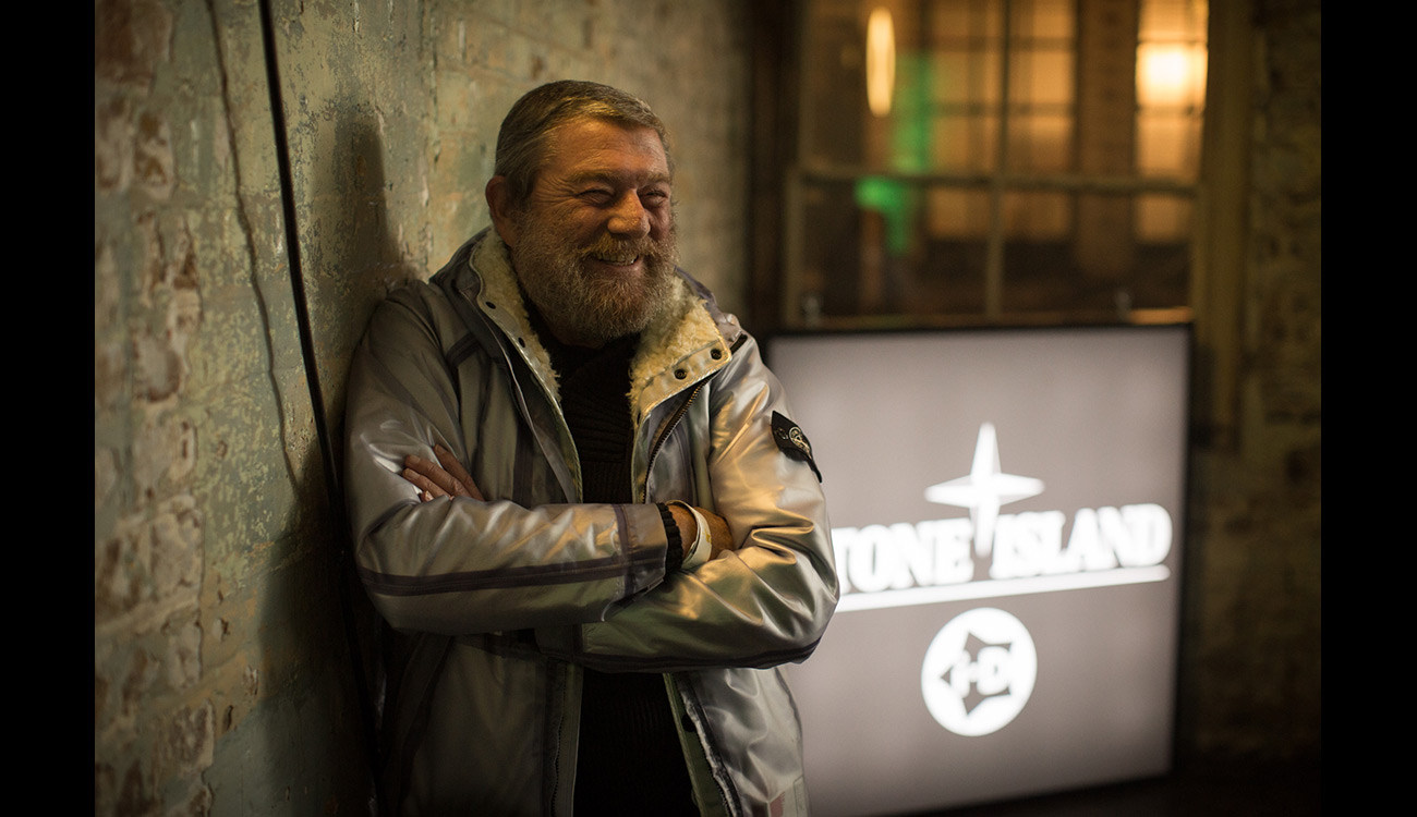 CEO of Stone Island Carlo Rivetti standing outside, leaning on a wall with his arms crossed over his chest and smiling.