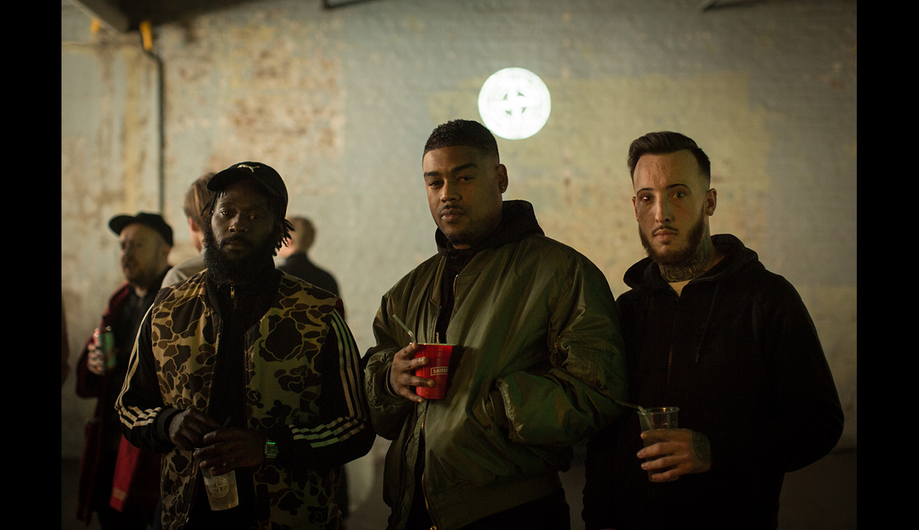 Three guys with drinks wearing different style jackets.
