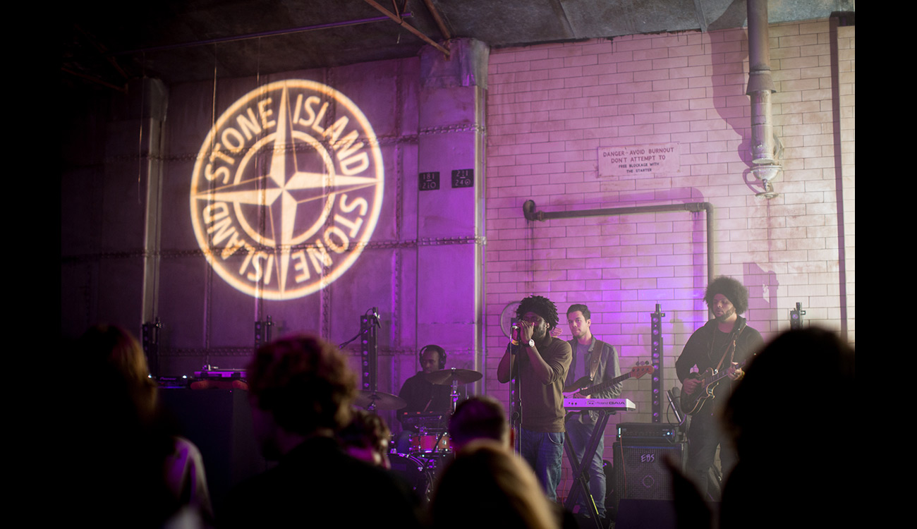 Live band playing under Stone Island compass logo projected on the wall behind them.
