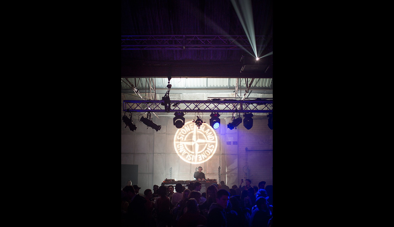 DJ seen mixing under the Stone Island compass logo projected on the wall.