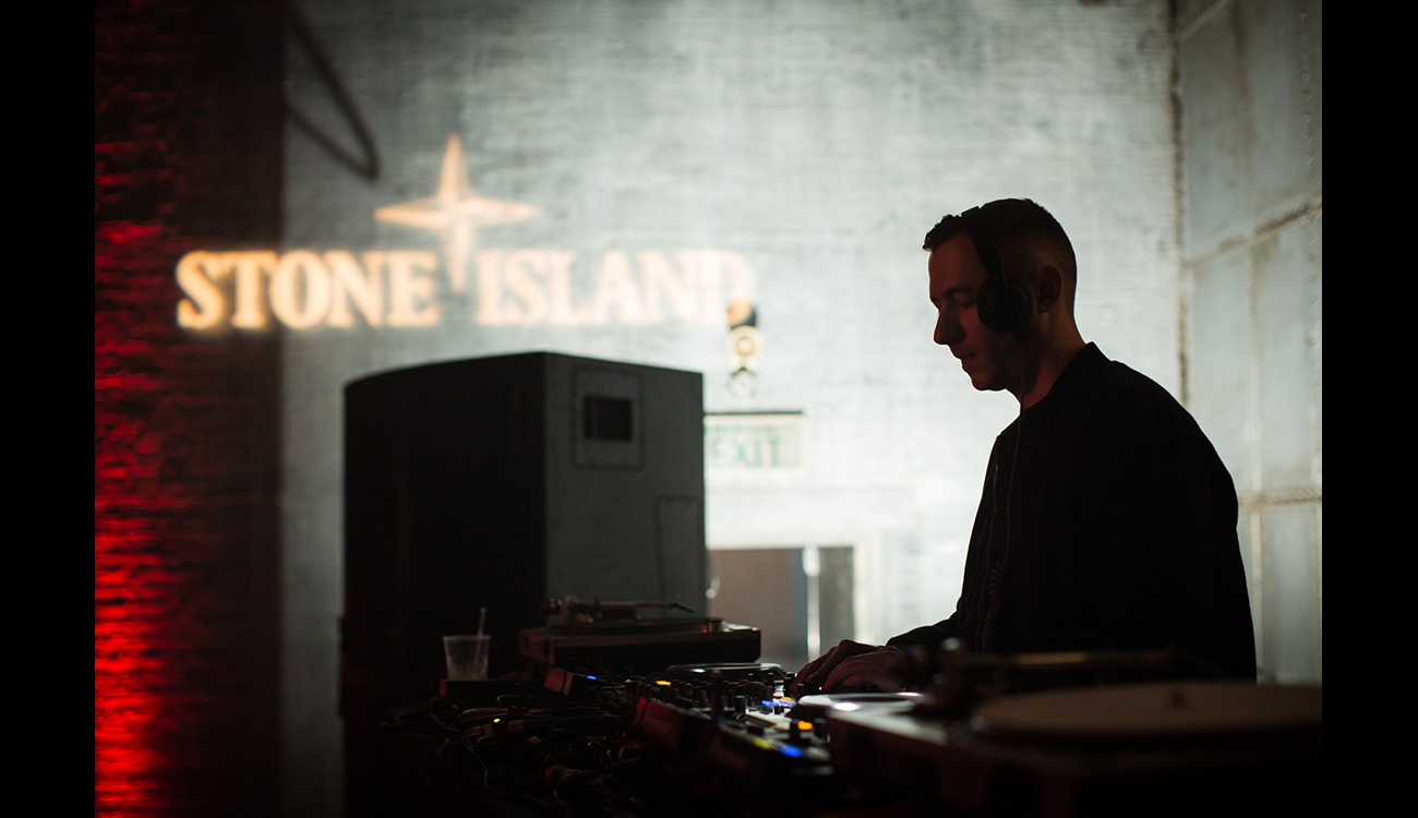 DJ seen mixing under Stone Island logo projected on wall.