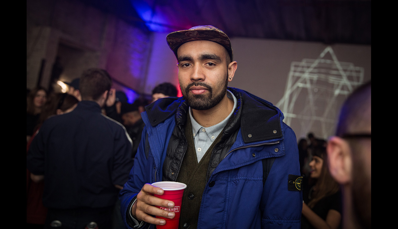 Guy in blue baseball cap and blue Stone Island jacket, holding a drink.