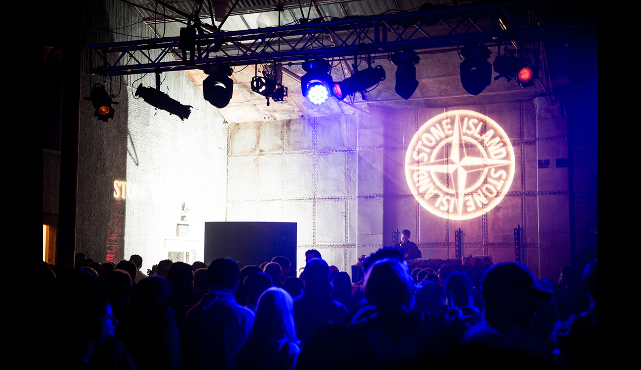 Stone Island compass logo projected on wall above DJ.