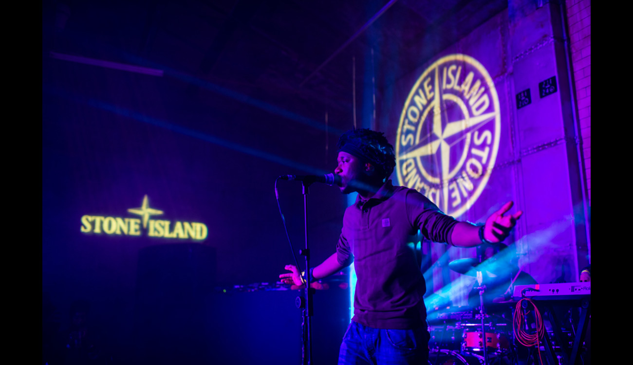 Guy standing in front of microphone with his arms wide open, with Stone Island compass logo projected on wall.