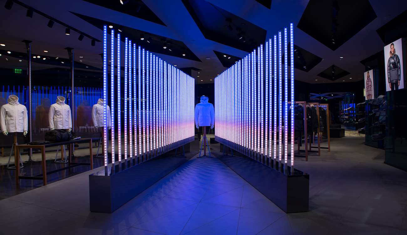 Dimly lit space with Stone Island jacket on mannequin sandwiched between two diagonal rows of poles lit up in blue.