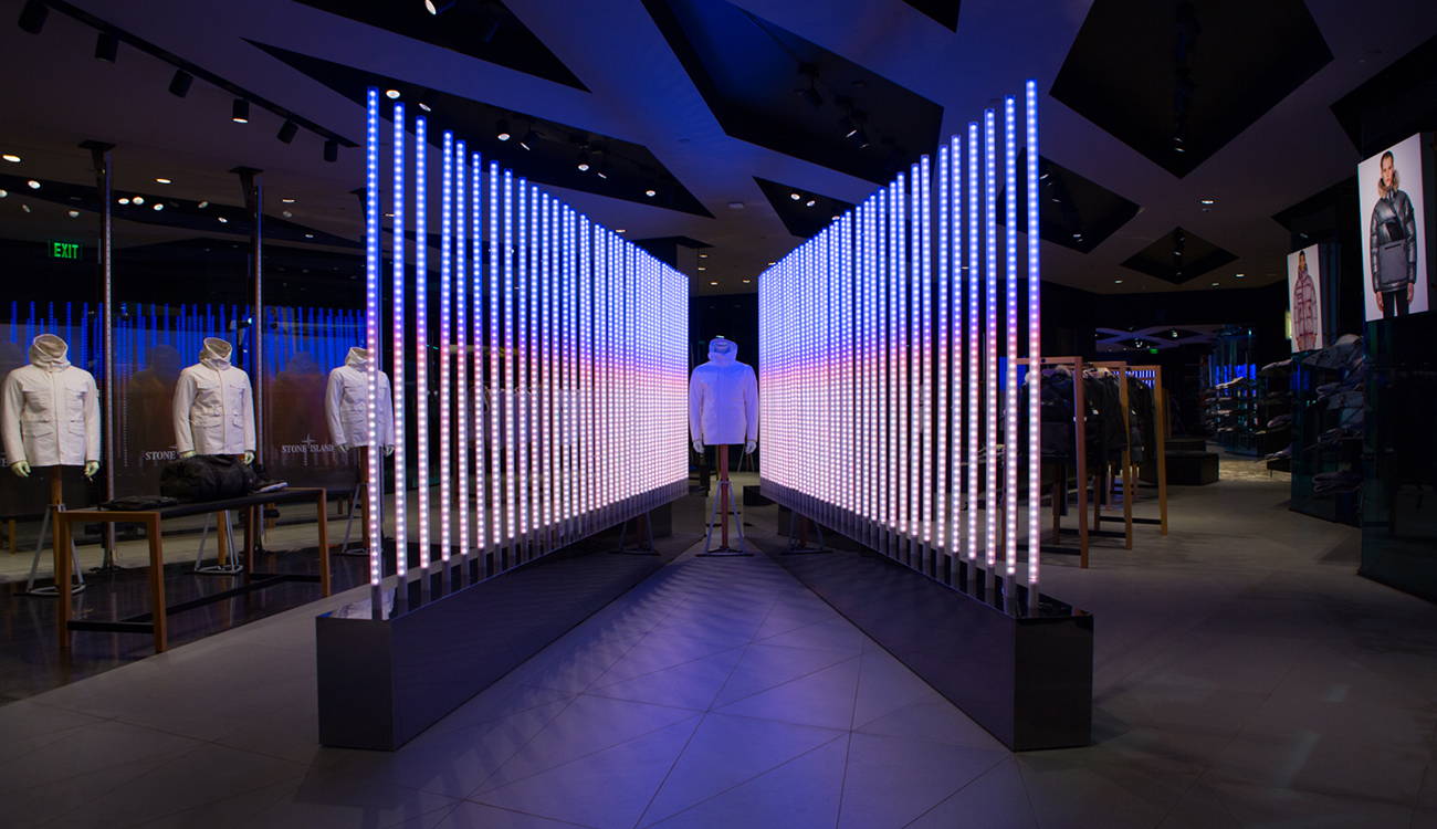Dimly lit space with Stone Island jacket on mannequin sandwiched between two diagonal rows of poles lit up in white and blue at the top.