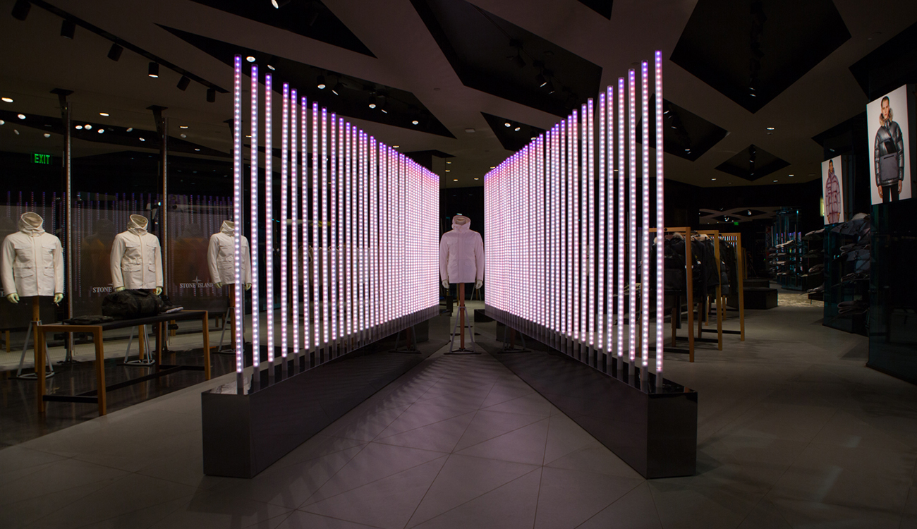 Dimly lit space with Stone Island jacket on mannequin sandwiched between two diagonal rows of poles lit up in white and pink.