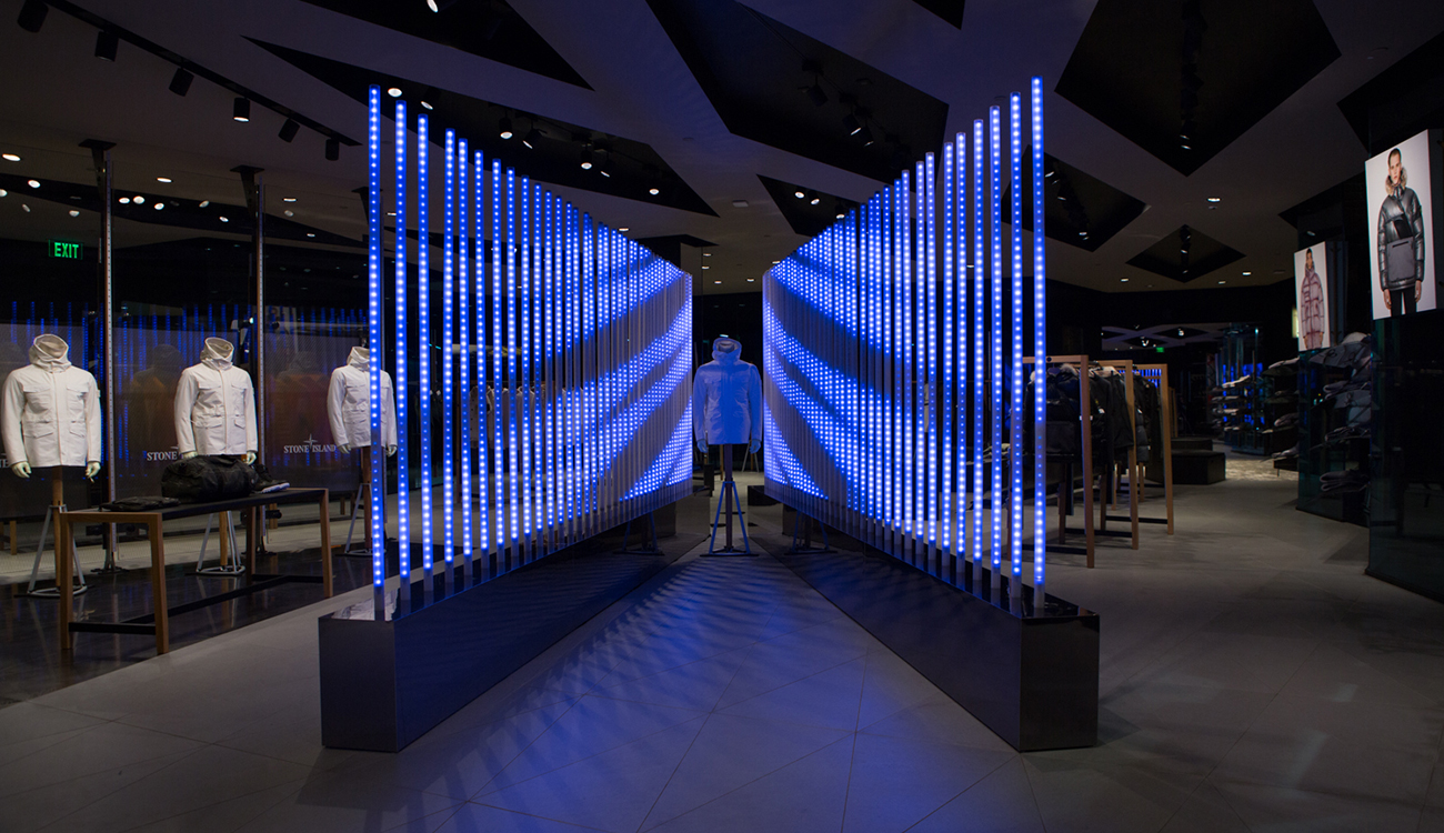 Dimly lit space with Stone Island jacket on mannequin sandwiched between two diagonal rows of poles lit with a blue, wing like design across the poles.