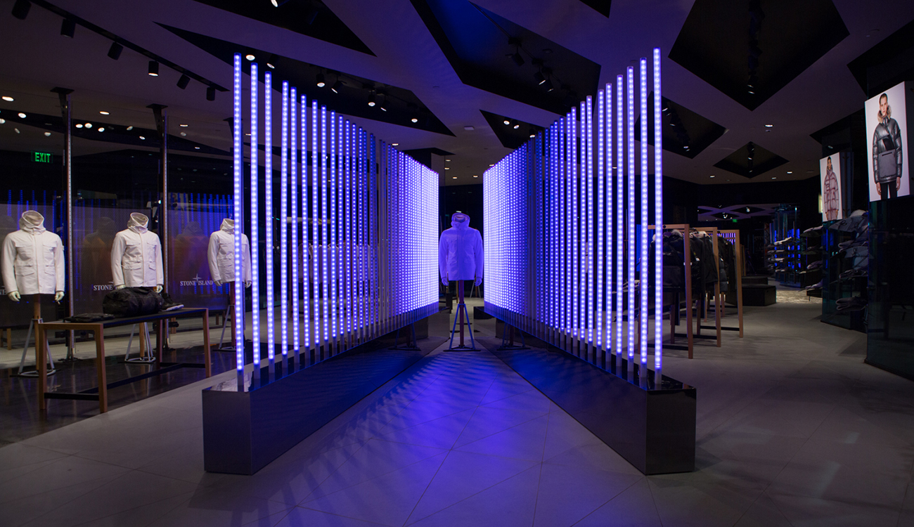 Dimly lit space with Stone Island jacket on mannequin sandwiched between two diagonal rows of poles lit up in blue except for the central poles.