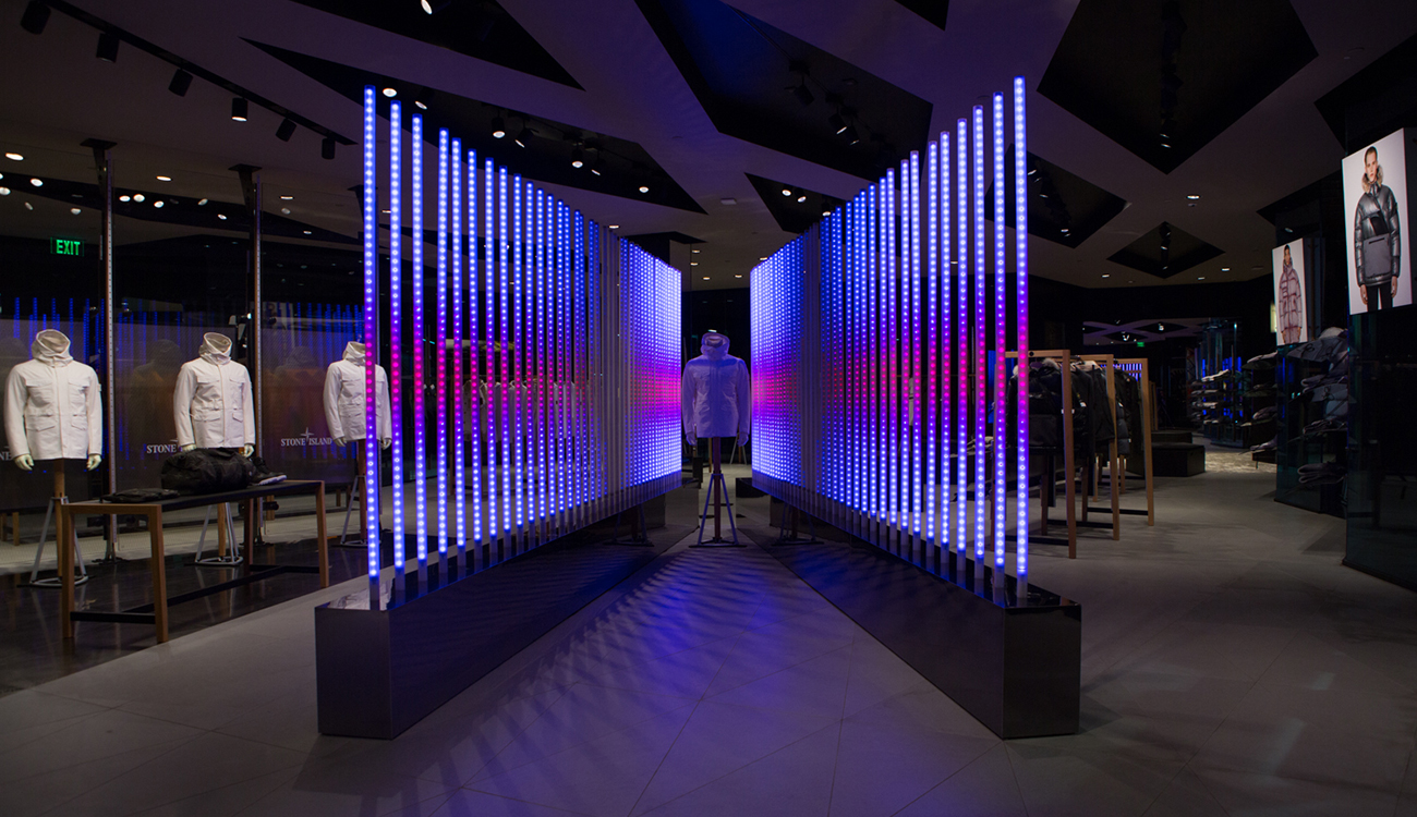 Dimly lit space with Stone Island jacket on mannequin sandwiched between two diagonal rows of poles lit up with blue at the top and bottom of the poles and pink at the center.