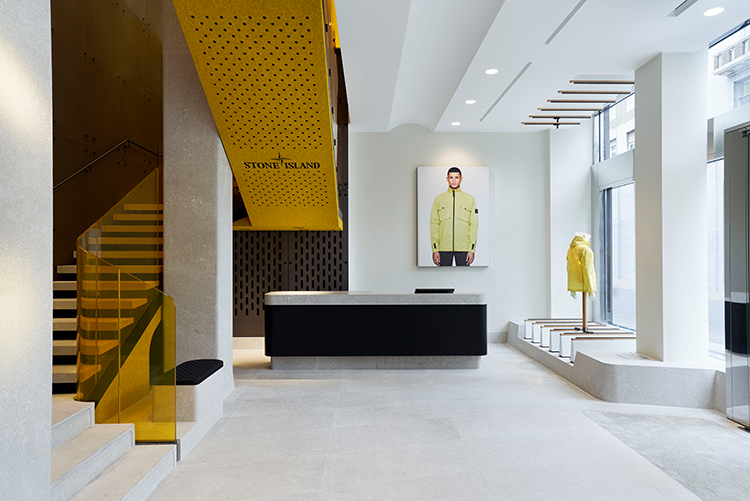 Modern store interior with white floor tiles, white ceiling, minimal furnishings and a yellow staircase.