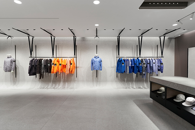 Merchandise displayed on minimalist store fittings, organized by color.
