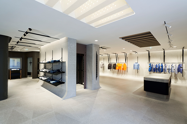 Wide view of store interior showing a black and white minimalist design and merchandise organized by color.