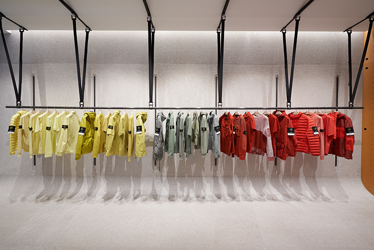Yellow, gray and red jackets and tops organized by color and displayed on industrial style clothes racks.