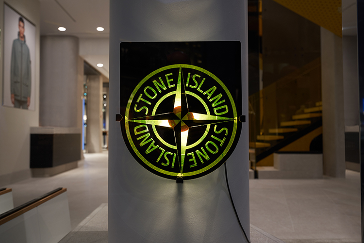 The Stone Island compass logo in black and green lit up on a wall.