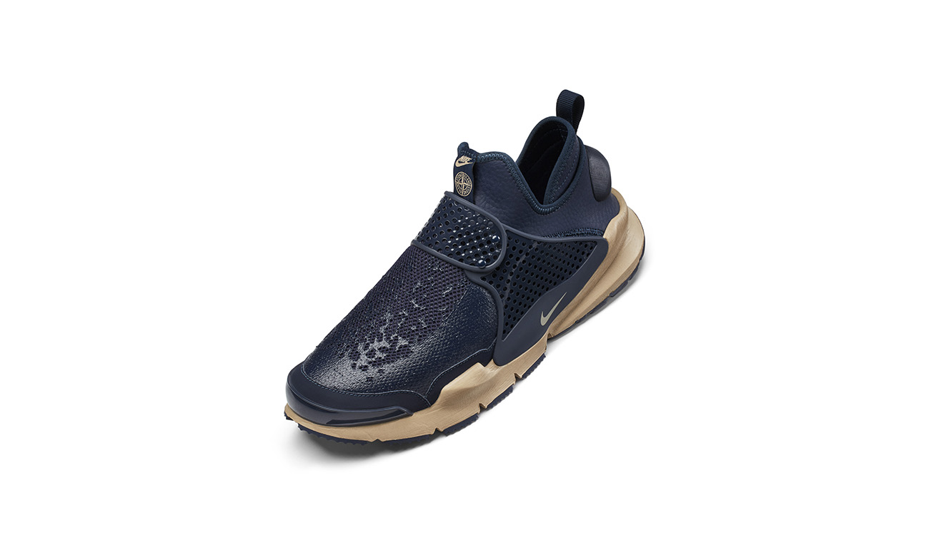 Left foot of mid navy, slip on sneakers in synthetic leather with mesh upper, midfoot strap and cream, chunky outsole.