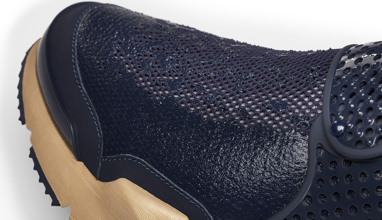 Close-up of mesh and outsole of mid navy, slip on sneaker in synthetic leather.