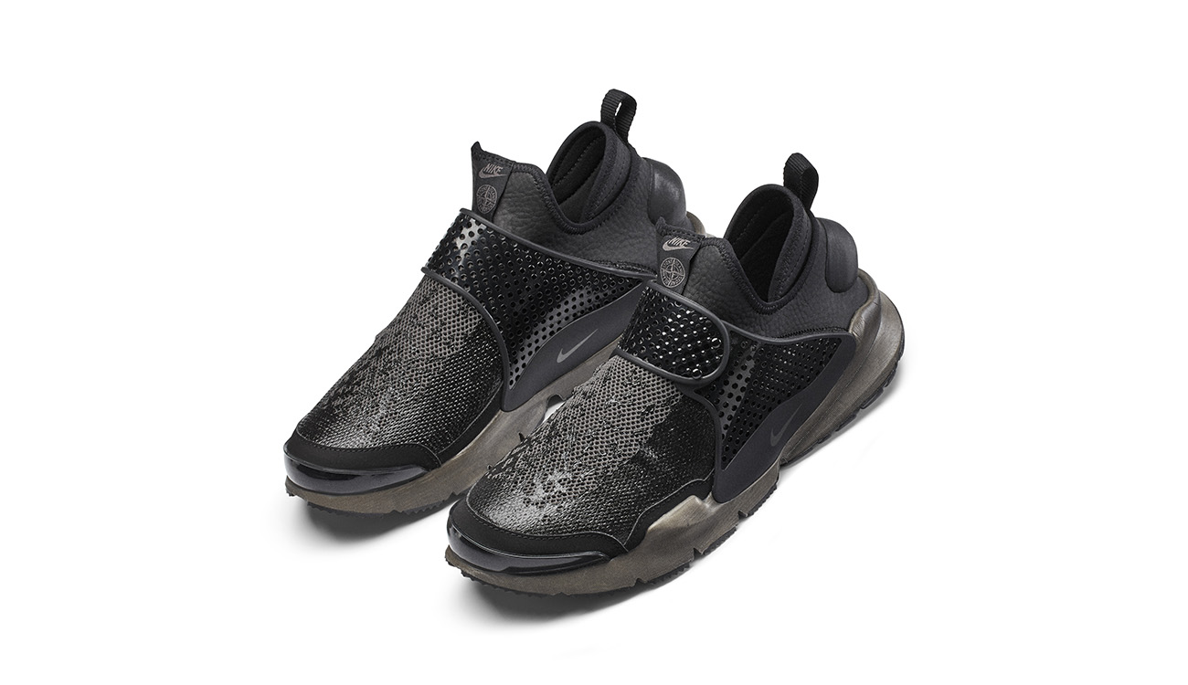 Pair of black, slip on sneakers in synthetic leather with mesh upper, midfoot strap and gray, chunky outsole.