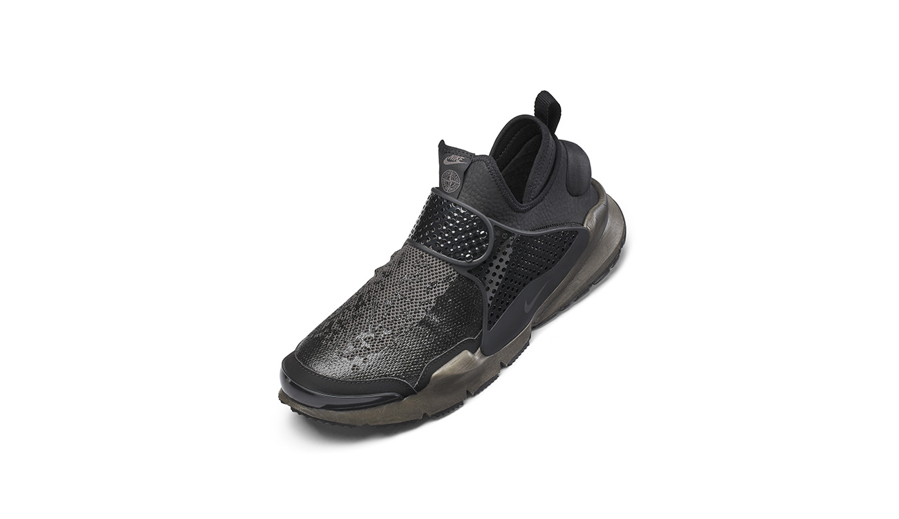 Left foot of black, slip on sneakers, in synthetic leather with mesh upper, midfoot strap and gray, chunky outsole.